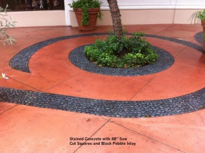 Stained-Concrete-with-48-Saw-Cut-Squares-and-Black-Pebble-Inlay