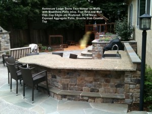 Kennesaw Ledge Stone Thin Veneer on Walls  with Bluestone Patio Inlay, Foot Rest and Wall Cap. Cap Edges are Routered. 3_16 Noiyo  Exposed Aggregate Patio. Granite Slab Counter Top